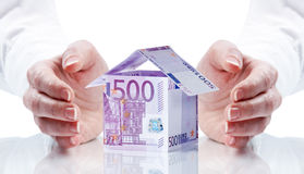 Money for house. Person's hands around a miniature house made of Euro banknotes Stock Photos