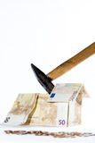 Money-house made of banknotes, coins and hammer Royalty Free Stock Photography