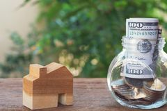 Money for housing. Coins and banknote in glass jar with greenery background. Copy space. Money for housing. Wooden house model, Coins and banknote in glass jar stock photos
