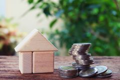 Money for housing. Piles of coins and wooden house model with green background. Copy space royalty free stock photography