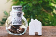 Money for housing. Wooden house model, Coins and banknote in glass jar with greenery background. Copy space stock images