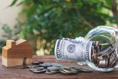 Money for housing. Wooden house model, Coins and banknote in glass jar with greenery background. Copy space royalty free stock photography