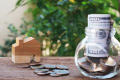 Money for housing. Wooden house model, Coins and banknote in glass jar with greenery background. Copy space royalty free stock image