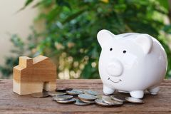 Money for housing. Wooden house model, piggy bank and pile of coins with greenery background. Copy space stock photo