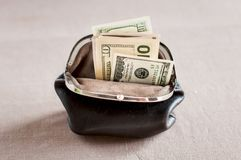 Money ina retro brown purse,. Over brown background Royalty Free Stock Photos