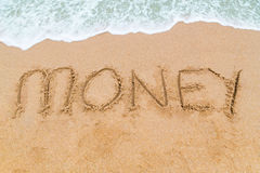 MONEY inscription written on sandy beach with wave approaching Royalty Free Stock Image