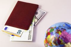 Money inside the passport and the globe is out of focus 2 stock photos