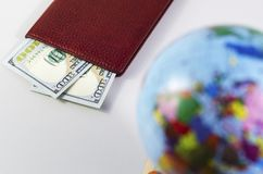 Money inside the passport and the globe is out of focus stock images