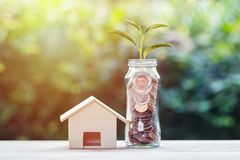 Money investment for home concept. Mini wood house model and coins in glass jar with growing plant on top on wooden table with green nature background. Home royalty free stock photography