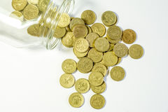 Money jar. Uk pound coins spilled from money jar Royalty Free Stock Photography
