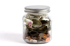 Money Jar. Clear glass jar filled with USA dollars and coins sit on a white background financial concept Stock Photography
