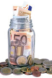 Money Jar. Overflow with Euro bank notes and coins against white background royalty free stock images