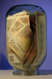 Money in jar. The jar overflowing with money, US currency and euros Stock Photography