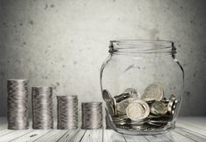 Money Jar with coins on wooden background royalty free stock photos
