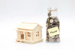 Money jar with coins and model wood house Royalty Free Stock Image