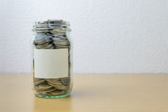 Money jar with coins on wood table Stock Photos