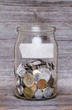 Money jar with coins on wood table Royalty Free Stock Photo