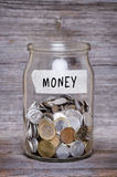 Money jar with coins on wood table Royalty Free Stock Images