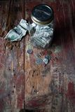 Money jar with dollars and change on old wooden table. Top view Stock Photo