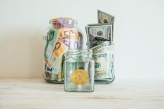 Money in jar euro dollars bitcoin Royalty Free Stock Image