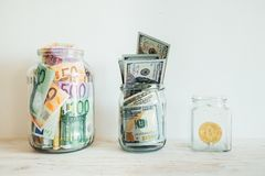 Money in jar euro dollars bitcoin Stock Photos