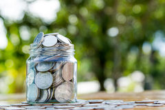 Money jar filled with coins on green bokeh. Saving money concept, Money jar filled with coins on green bokeh background stock images