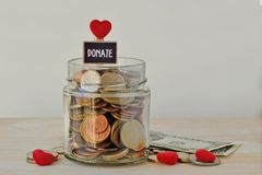 Money jar full of coins with Donate label and hearts - Charity concept royalty free stock photos