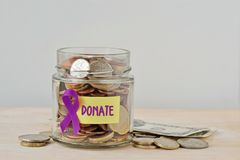 Money jar full of coins with violet ribbon and Donate label - Concept of Alzheimer, Pancreatic cancer, Epilepsy , Hodgkin`s. Money jar full of coins with violet stock image