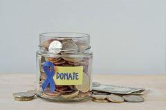 Money jar full of coins with violet ribbon and Donate label - Concept of prostate cancer charity and research fund. Money jar full of coins with violet ribbon stock images