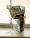 Money Jar. One hundred dollar bills hanging out of a money jar. A glass jar with money spilling out of it and a wishbone lying next to it Royalty Free Stock Photography
