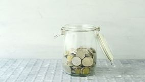 Money jar saving concept. Coins falling into the money jar, then decrease till empty stock video