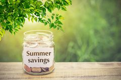 Money in the jar on wooden table and text Summer Savings. With filter effect retro vintage style. The concept of saving money for tourism in the summer Royalty Free Stock Photo