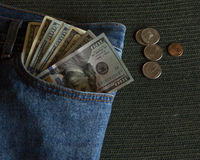 Money in jeans pocket. One hundred dollar bills hanging out of a pair of jeans pocket Royalty Free Stock Image