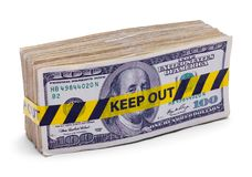 Money Keep Out. Wad of Hundred Dollar Bills with Keep Out Tape Isolated on White stock photo