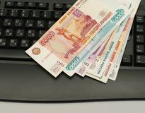 Money on key board. Russian currency bonds lie on black keypad Royalty Free Stock Image