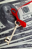 Money key. Golden skeleton key on a red cord with a bow on a dollar background royalty free stock image