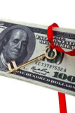 Money key 2. Golden skeleton key on a red cord with a bow on a dollars. Isolated on white Royalty Free Stock Image