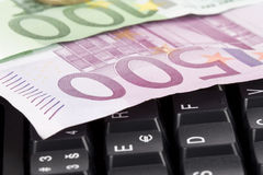 Money on a keyboard Stock Images