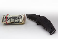 Money and knife on white background. Royalty Free Stock Photo