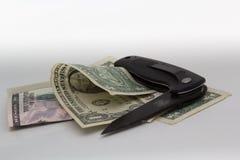 Money and knife on white background. Stock Image