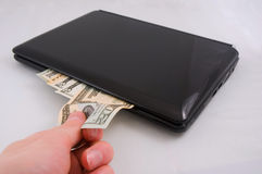Money and laptop. Withdrawing notes from or inserting notes into a closed laptop. A money metaphor Royalty Free Stock Image