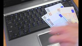 Money on a laptop keyboard stock video footage