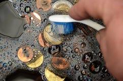 Money Launder. Black Euro coins being washed, suggesting the term `whitewash of black money royalty free stock image
