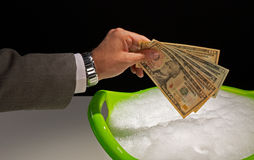 Money laundering. Putting dollar banknotes to soak, money laundering concept Stock Photos