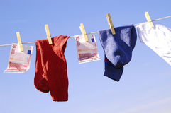 Money laundering. Photo of money and clothes hanging on the clothesline on the blue sky stock photography