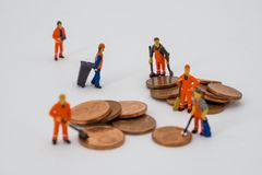 Money laundering concept. Miniature people cleaning coins Royalty Free Stock Photos
