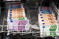 Money laundering in the dishwasher. Money laundering with european banknotes Royalty Free Stock Photo