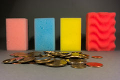 Money laundering. Stack of colorful sponges in a row and  coins Royalty Free Stock Photography
