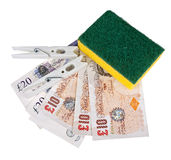 Money laundering UK pounds sterling. Banknote with scouring pad and pegs. White background Stock Photography