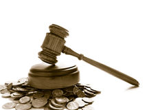 Money law. Judges law gavel on a pile of coins, over white Royalty Free Stock Photography
